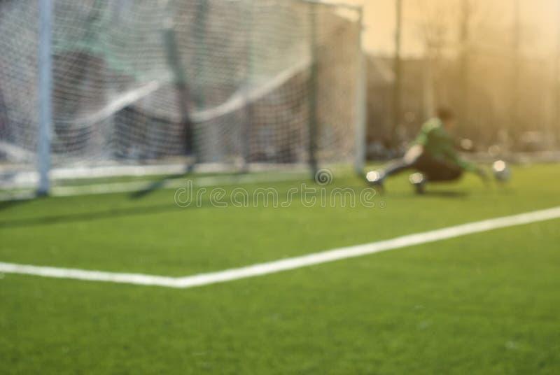 Suddig fotbollbakgrund: målvakten fångar bollen under modigt ögonblick arkivbild