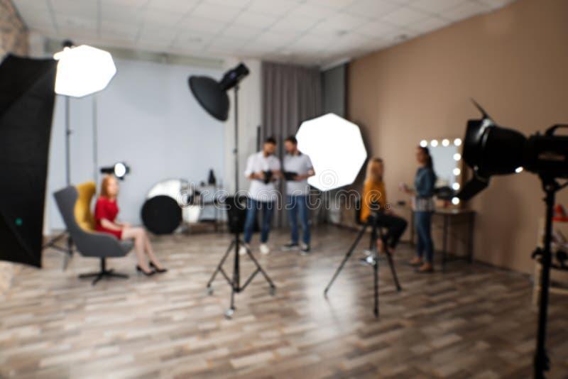 Suddig fotostudio med yrkesmässig utrustning och laget fotografering för bildbyråer