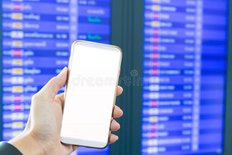 Suddig hand som rymmer den smarta telefonen för att kontrollera kampen för transport i flygplats arkivfoton