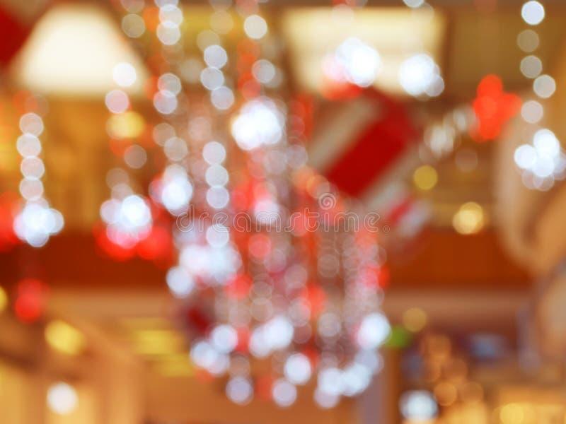 Suddig inre med bokeh: köpcentret tände och dekorerade festively med skinande girlander för ferier, jul a royaltyfria foton
