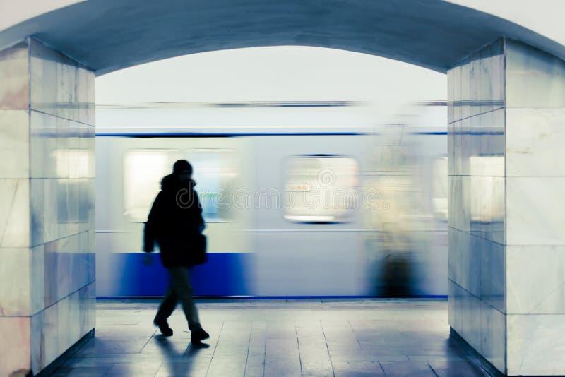 Suddig kontur av en gå man på en Moskvagångtunnelstation mot bakgrunden av ett avtågande drev fotografering för bildbyråer