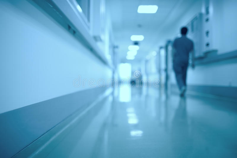 Suddig medicinsk bakgrund Rörande mänskligt diagram i sjukhuskorridoren royaltyfria bilder