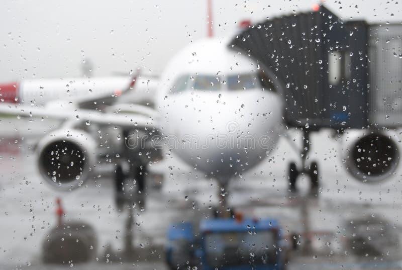 Suddig passagerarflygplan under regn royaltyfri bild