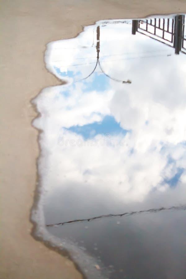 Suddig reflexion för spegel efter ett regn av den blåa molniga himlen i en pöl på asfalten royaltyfri bild