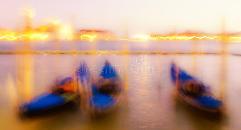 Suddig sikt för natt på de förtöjde gondolerna på pir nära piazza San Marco i Venedig royaltyfri foto