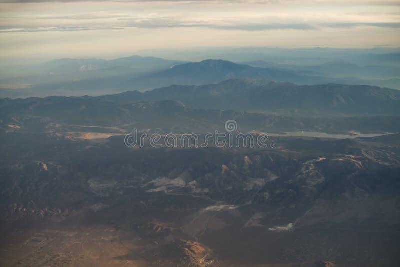 Suddig sikt från nivån under flyg över Kalifornien berg i solnedgång arkivfoton
