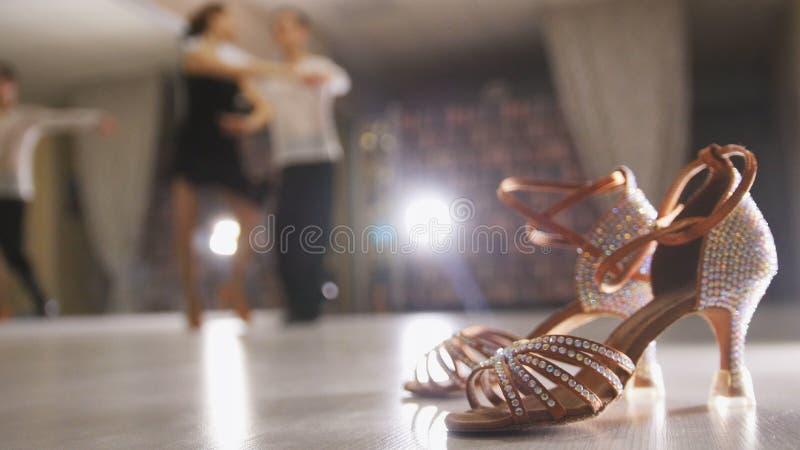 Suddig yrkesmässig latinsk dans för man- och kvinnadans i dräkter i studion, balsalskor i förgrunden fotografering för bildbyråer