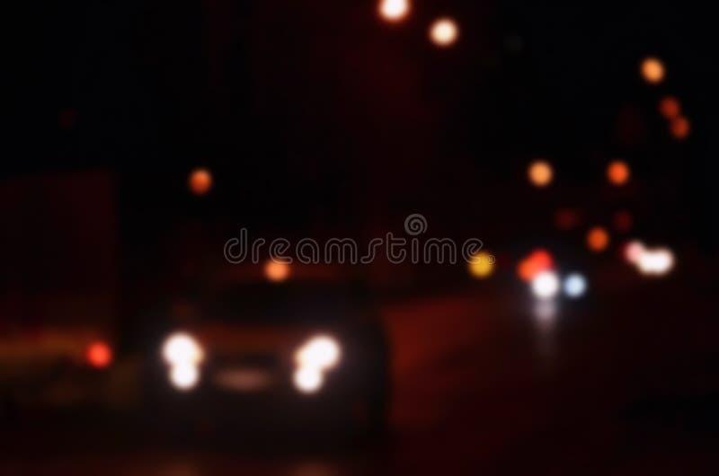 Suddiga Defocused ljus av trafik på en våta regniga City Road på natten - pendling på rusningstidConceptnAbstract bokeh från bill royaltyfri fotografi