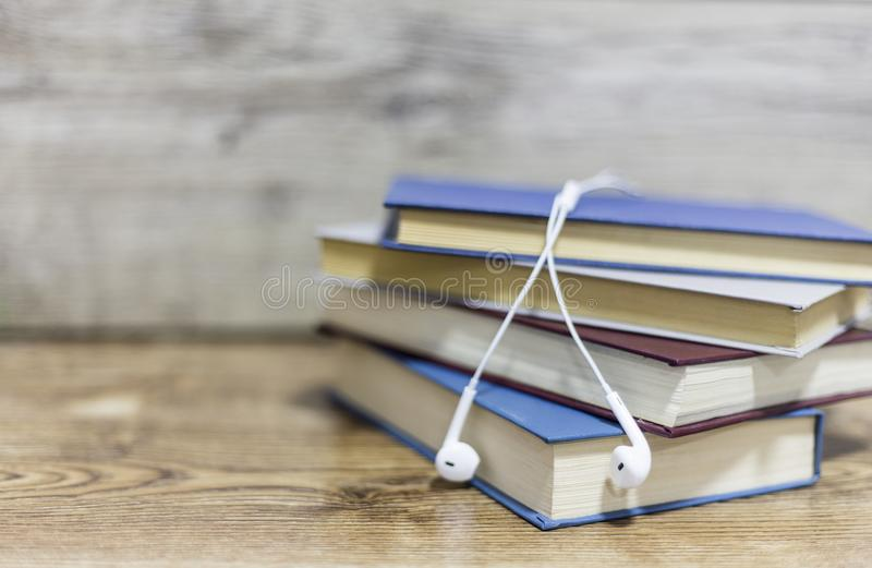Suddiga fyra böcker och hörlur på trätabellen arkivbild