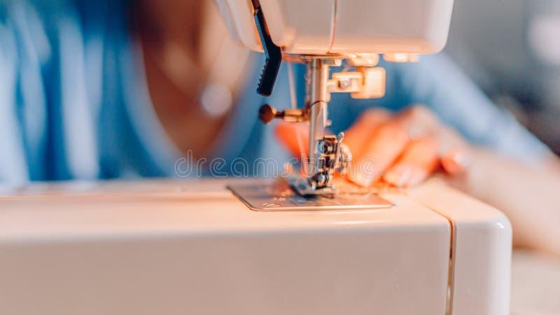 Suddiga händer av att sy process Kvinnliga händer som syr tyg på maskinen royaltyfri foto