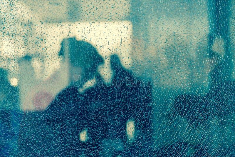 Suddiga konturer av folk bak brutet exponeringsglas Bot - ingrepp av sprickor idérik bakgrund Kvinnligt profilera Töm designmalle royaltyfri bild
