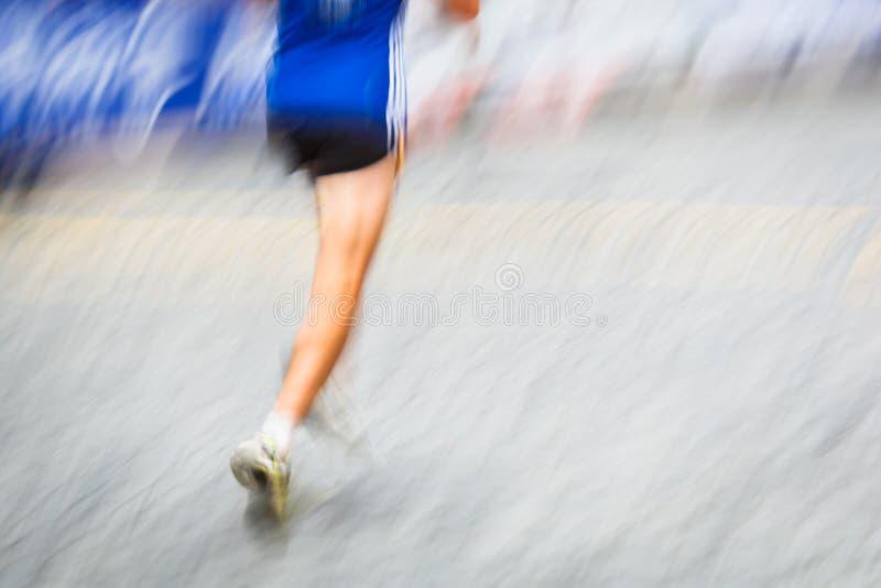 Suddiga löpares för rörelse fot i en stadsmiljö royaltyfria bilder