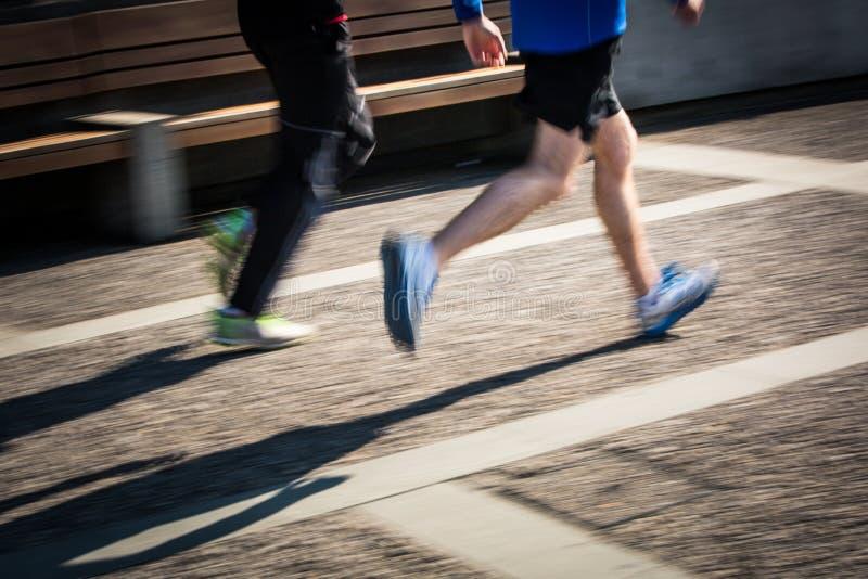 Suddiga löpares för rörelse fot i en stadsmiljö royaltyfri fotografi