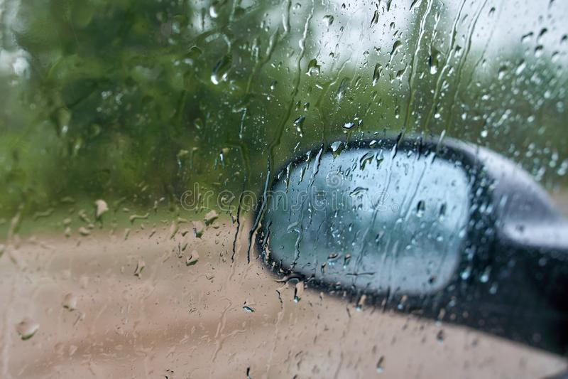 Suddiga regndroppar på sidofönstret av bilen Bak exponeringsglaset kan du se sidospegeln med blured reflexioner royaltyfri fotografi