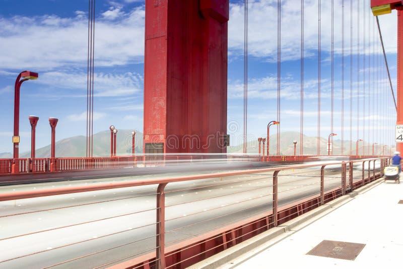 Suddiga slingor av bilar och folk som förbigår på Golden gate bridge arkivfoto