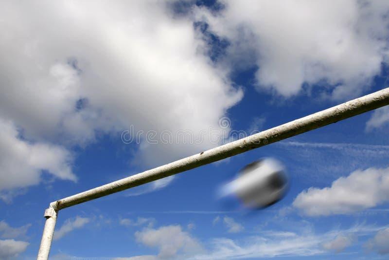Suddighet fotboll och goalpost mot en molnig sky arkivbild