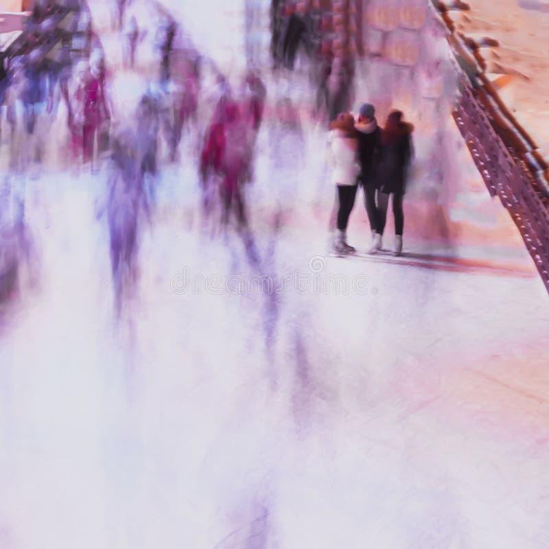 Suddighetsbilden av tre flickvänner på skridskoisbana mot bakgrundstaden parkerar, folk, vintern, kamratskap, sport och arkivbilder
