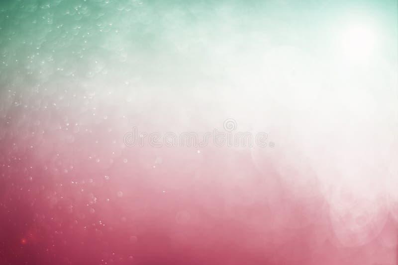 Suddigt abstrakt bokehljus av klipsk vattenbakgrund, jul två signalfärger royaltyfria bilder