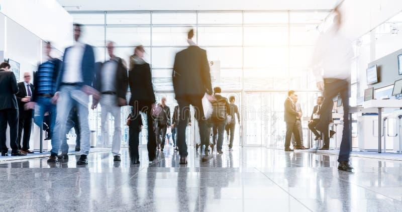 Suddigt affärsfolk på en korridor för handelmässa royaltyfri foto