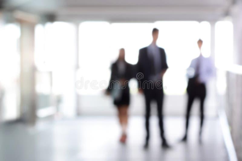 Suddigt affärsfolk som står i byggnadskorridor fotografering för bildbyråer