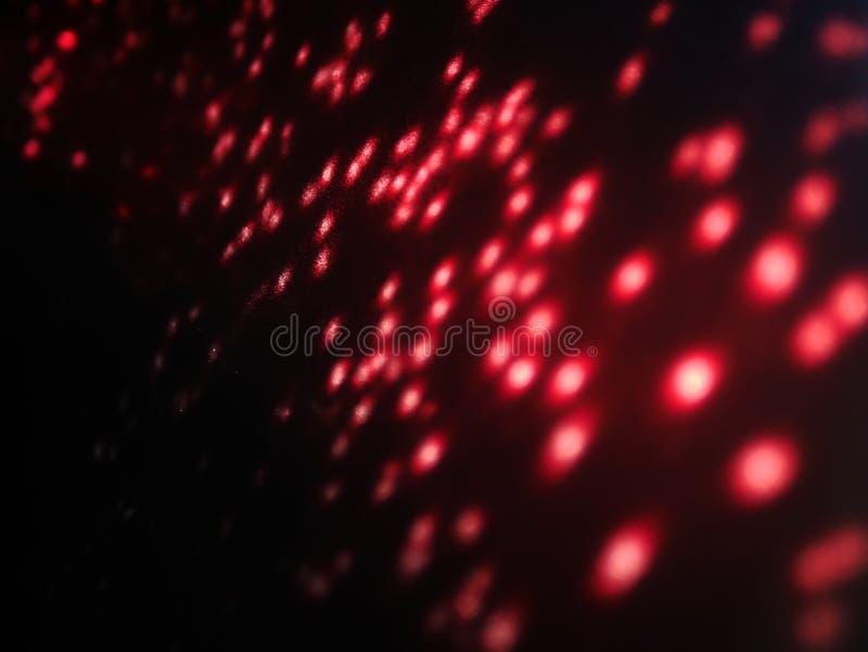 Suddigt rött defocused ljust ljus Lens signalljus Skinande fläckar Stranda av hår vänder mot in royaltyfri bild