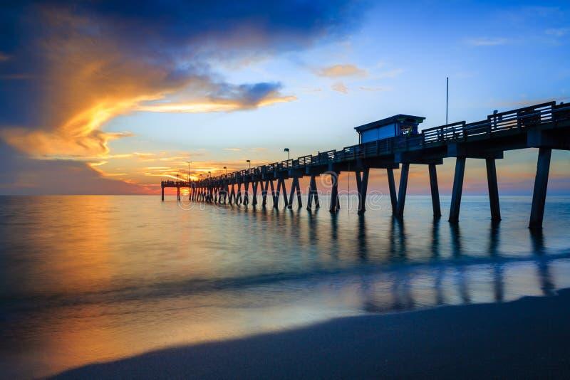 Suddigt vatten mjuknar som soluppsättningarna över den Venedig pir i Florida royaltyfri bild