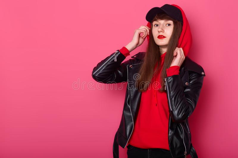 Sudio portrait of young beautiful fashionable teenager girl wearing leather jacket, red hoody and black cap, posing isolated over stock photo
