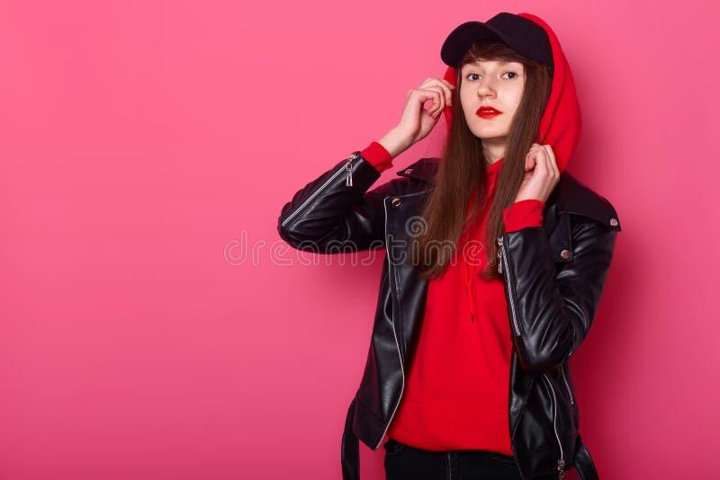 Sudioportret van jong mooi modieus tienermeisje dat leerjasje, rood hoody en zwart GLB, over geïsoleerd stellen draagt stock foto