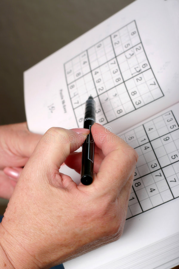 Sudoku. Woman figuring out a sudoku puzzle royalty free stock image
