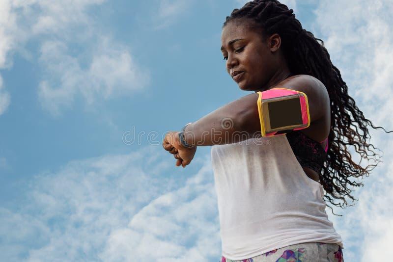 Sudorazione africana sportiva della donnaÂ dopo l'esercitazione il giorno caldo di estate sopra il fondo del cielo blu immagini stock libere da diritti
