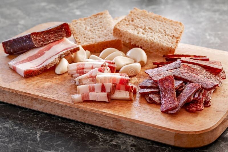 Sudzhuk affumicato della salsiccia con bacon, aglio e pane salati fotografia stock