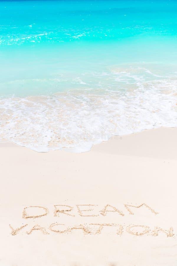 Sueñe escrito en la playa arenosa con la ola oceánica suave en fondo imágenes de archivo libres de regalías