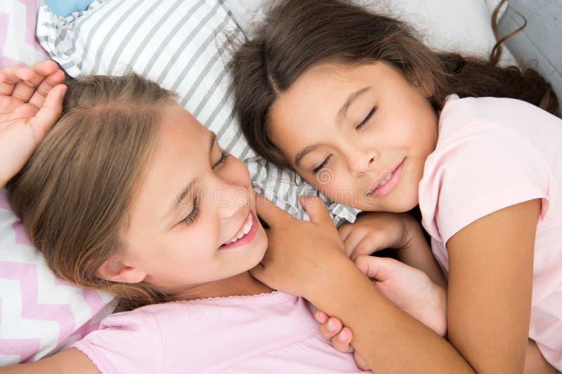 Sueño agradable en su mente Las muchachas se caen dormido después de partido de pijamas en dormitorio Las muchachas tienen sueño  foto de archivo libre de regalías
