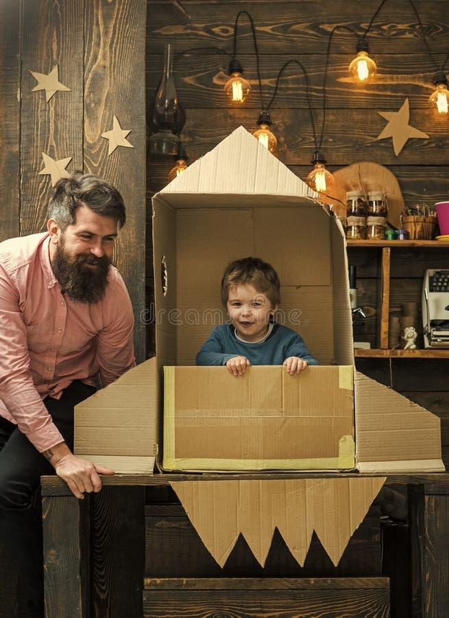 Sueño americano El juego del muchacho con el papá, padre, pequeño cosmonauta se sienta en el cohete hecho fuera de la caja de car fotos de archivo libres de regalías