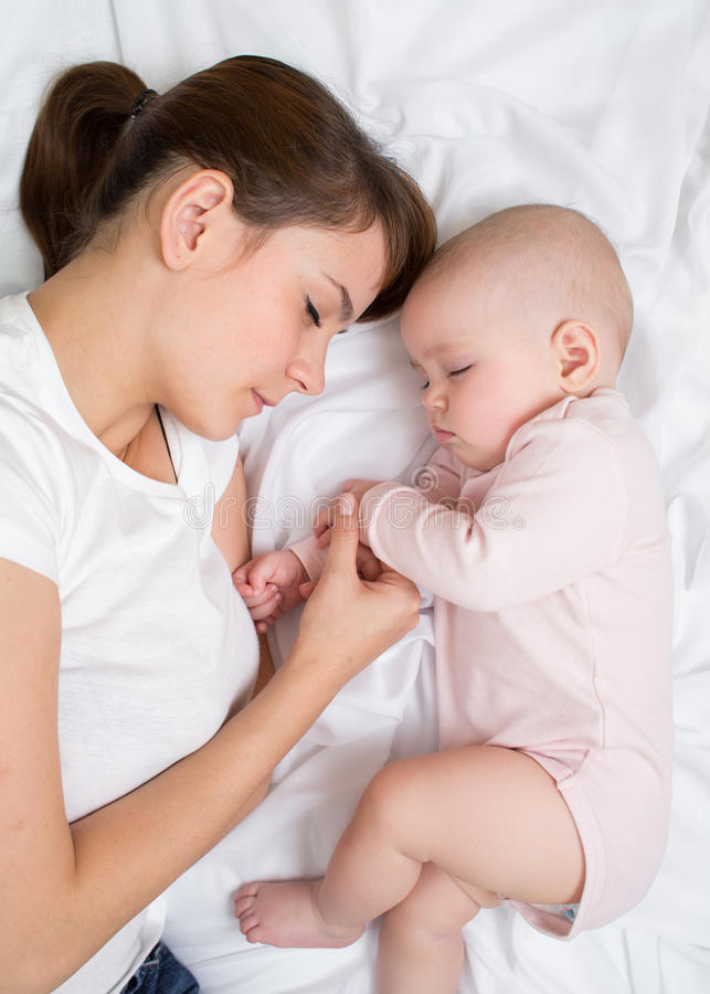 Sueño de la madre y del bebé en cama junto imagenes de archivo