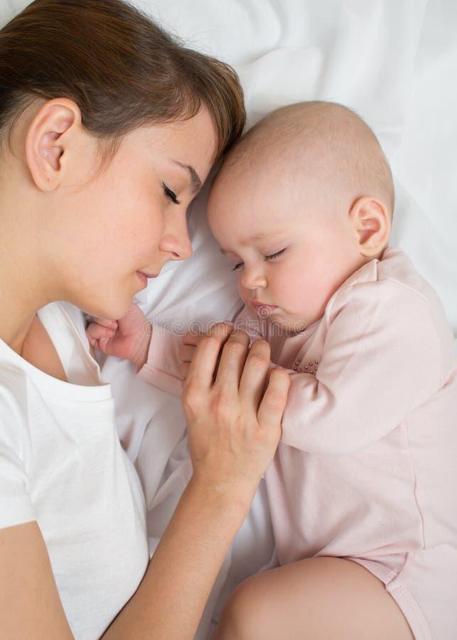 Sueño de la madre y del bebé en cama junto fotografía de archivo libre de regalías