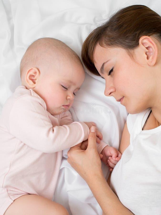 Sueño de la madre y del bebé en cama junto imagen de archivo libre de regalías
