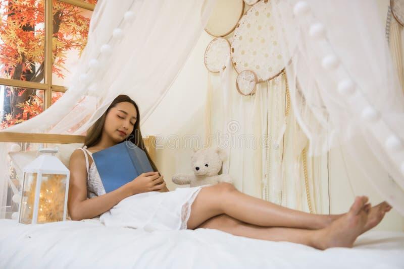 Sueño de la mujer en el libro de la cama y del control fotografía de archivo libre de regalías