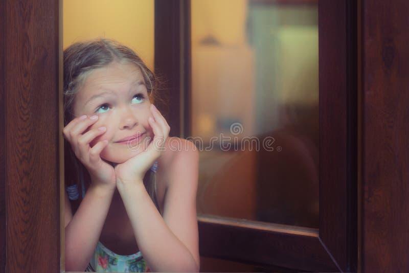 Sueño de la niña linda por la ventana imagen de archivo libre de regalías