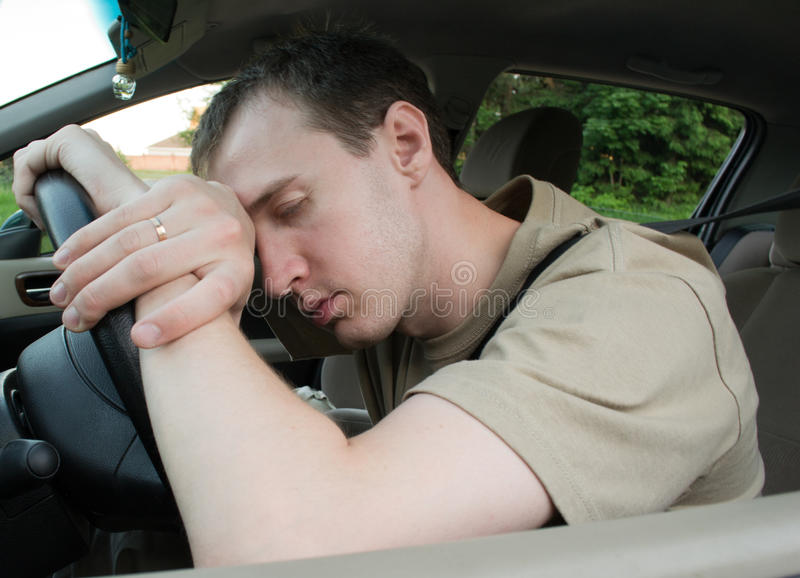 Sueño del hombre en un coche fotografía de archivo