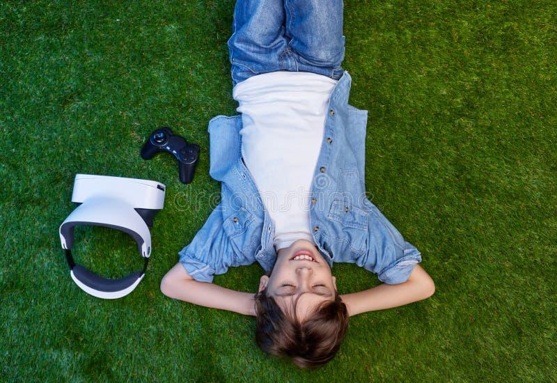 Sueño del niño en prado con las auriculares de VR imágenes de archivo libres de regalías
