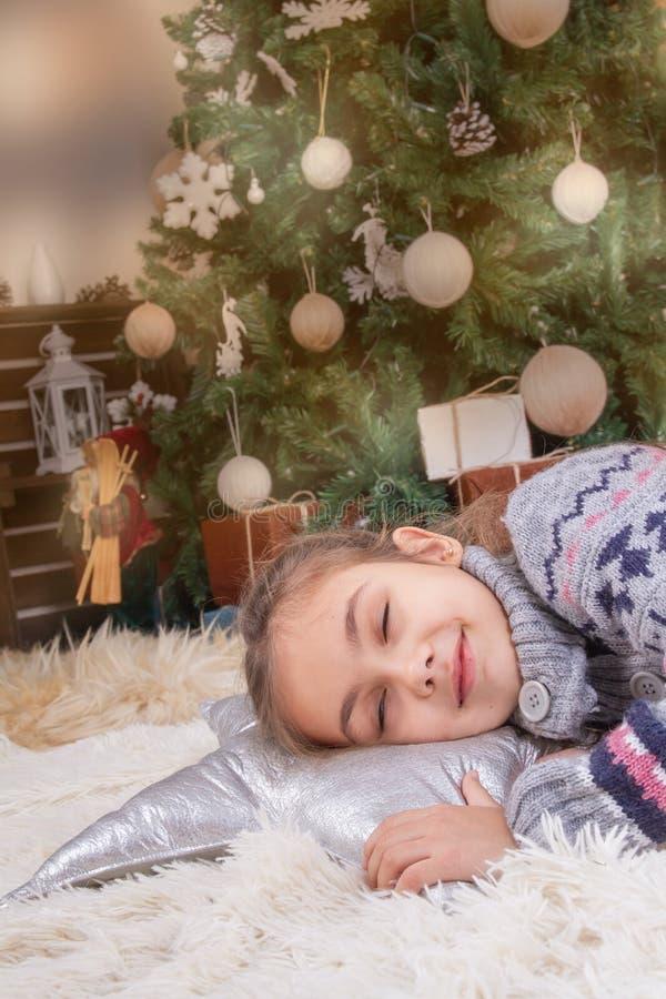Sueño el dormir de la muchacha del niño con emociones felices bajo Navidad de imagen de archivo libre de regalías