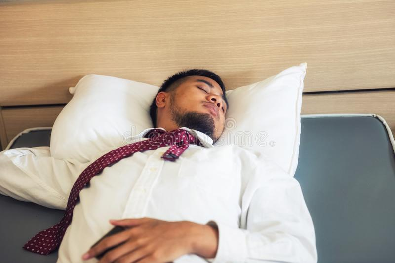 Sueño indio cansado del hombre de negocios en cama del hotel imagen de archivo