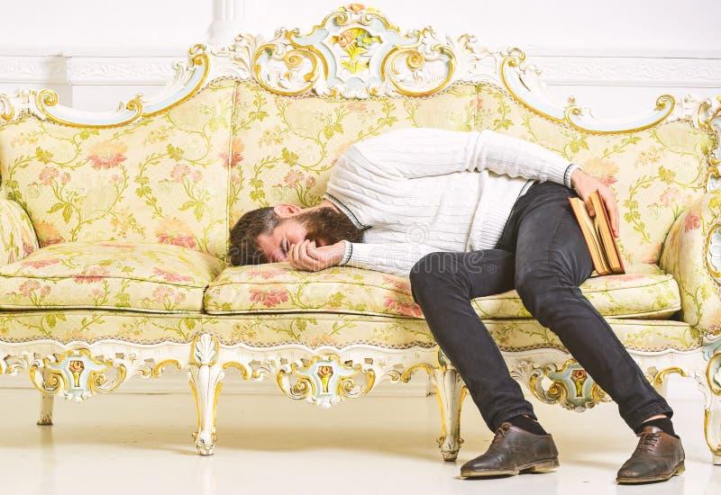 Sueño machista con el libro a disposición Concepto aburrido de la literatura El hombre con la barba y el bigote ponen en el sofá  foto de archivo