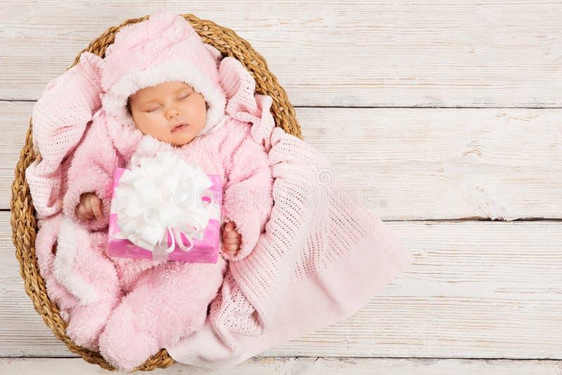 Sueño recién nacido del bebé con la actual caja de regalo, niño durmiente, rosa fotografía de archivo
