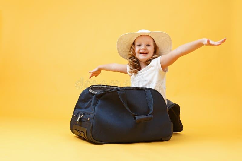 Sueños de viaje Una niña pequeña se sienta en una maleta y juega al piloto del avión y al viajero Fondo amarillo fotografía de archivo