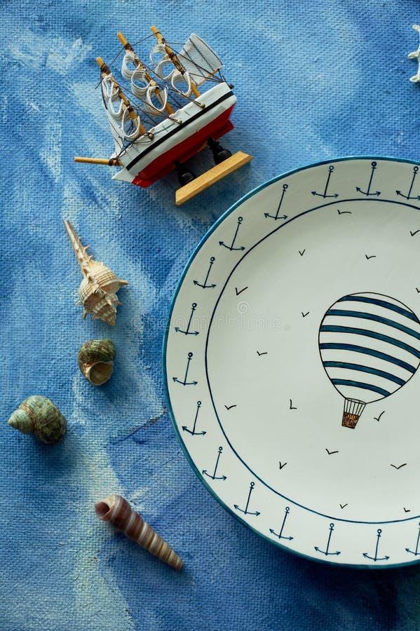 Sueños del mar y del viaje, una placa con un globo, cáscaras, una nave de madera En una lona del azul de cielo fotos de archivo