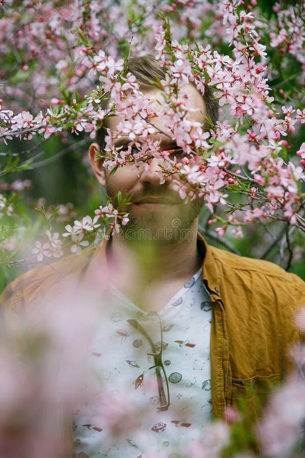 Sueños elegantes lindos jovenes del individuo en flores rosadas verdes y enormes de la almendra fotografía de archivo