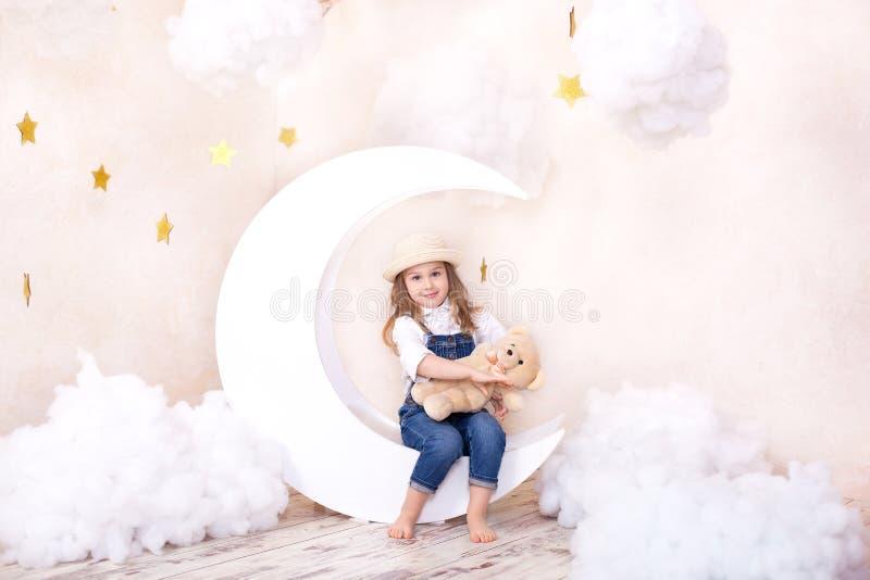 Sue?os dulces Poco muchacha linda que se sienta en la luna con las nubes y las estrellas con un oso de peluche en sus manos y jug fotografía de archivo