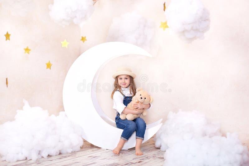 Sue?os dulces Poco muchacha linda que se sienta en la luna con las nubes y las estrellas con un oso de peluche en sus manos y jug imagenes de archivo